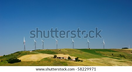 Row of wind turbines on the top of hill