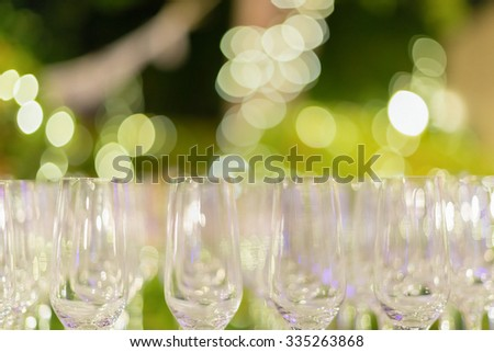 Row of wine glasses in green background painted with beautiful bokeh. - stock photo