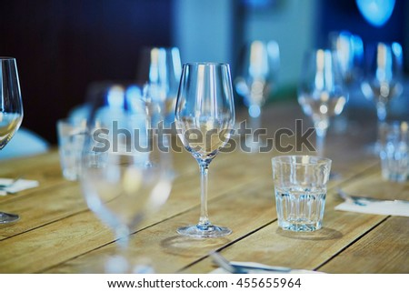 Row of wine glasses on the table in restaurant, bar or et wedding reception - stock photo
