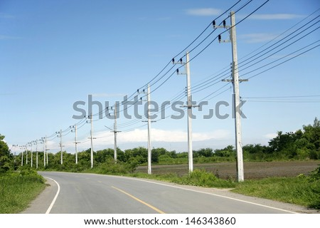 row of wire pole inside road on countryside with blue sky  - stock photo