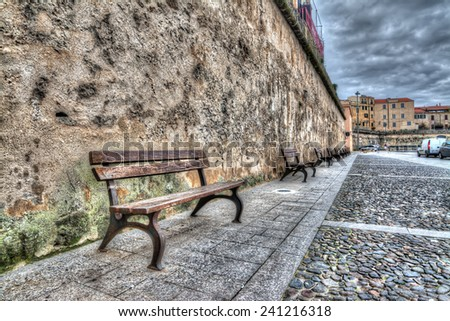 row of wooden benches in Alghero harbor. - stock photo