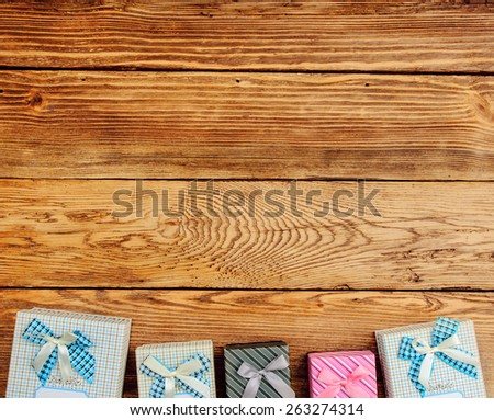 Row of Wrapped Gift Boxes Arranged at Top of Image with Ample Copy Space on Wooden Background as seen from Above - stock photo