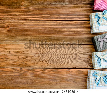 Row of Wrapped Gift Boxes Arranged Vertically Along Side of Image with Copy Space on Wooden Background from Above - stock photo