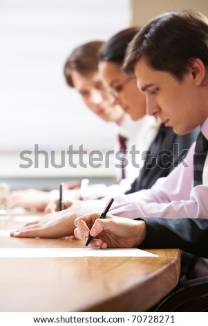 Row of writing people at table
