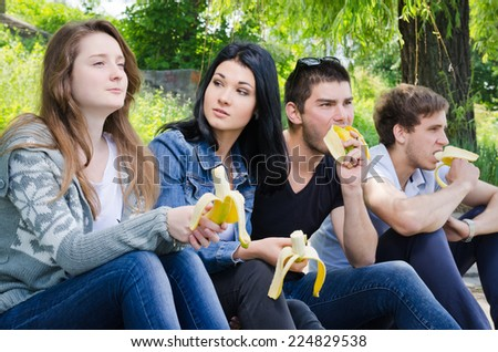 Row of young college friends sitting together watching an event with focus to the middle couple - stock photo