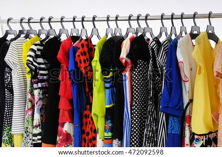 Row Variety of casual Female clothing hanging on hangers on black