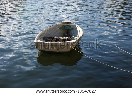 Rowboat drifting at anchor on the river - stock photo