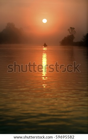 Rowboat in the sunset over the river.