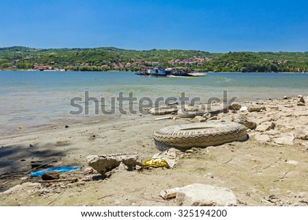 Rowboat tied to ferry is loaded with agricultural machines travel across the river. - stock photo