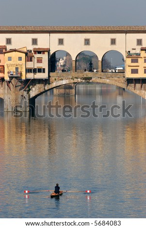 Rower on the river Arno in Florence, with Ponte Vecchio in the background. The golden illumination of the bridge in the morning light is reflected in the water. - stock photo