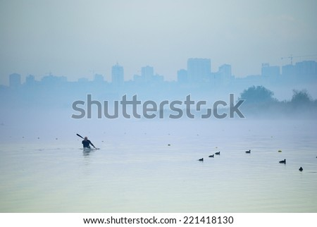 Rower sailing boat on a rowing canal in the fog - stock photo
