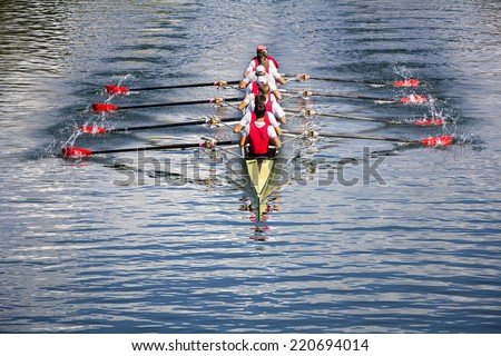 Rowers in eight-oar rowing boats on the tranquil lake - stock photo