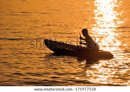 Rowing alone at sunset in golden hour at Koh Lipe, Thailand - stock photo