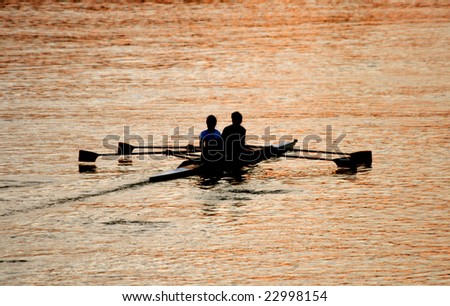 Rowing at sunset - stock photo