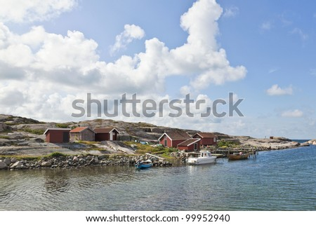 Rowing boat at the pier on the rocky coast - stock photo