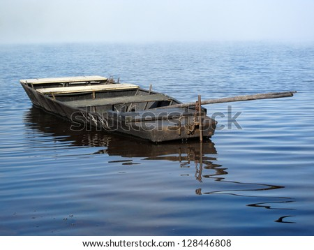 Rowing boat in morning fog on the lake.