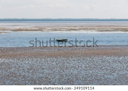 Rowing boat in the Wadden Sea in the North Sea nearby the Hallig Langeness. Because of the tides, that boat is aground. The Hallig is located in the district of north Friesland, Germany  - stock photo