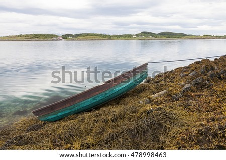 Rowing boat laying on rocks covered by seaweed, after sea level has fallen at low tide. Photographed at Norwegian coast, Helgeland.
