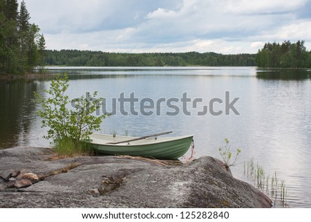 Rowing boat moored on the lake in the woods (Finland) - stock photo