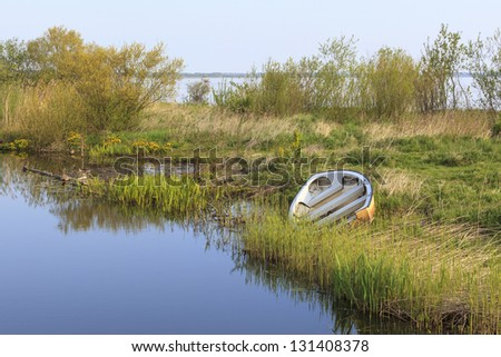 Rowing boat on beach of the river - stock photo