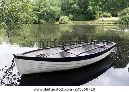 Rowing boat on placid river; small rowboat moored on riverbank; excellent copy space. - stock photo