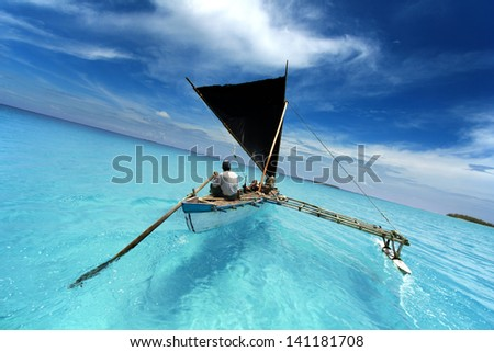 rowing boat sailing in a tropical lagoon - stock photo