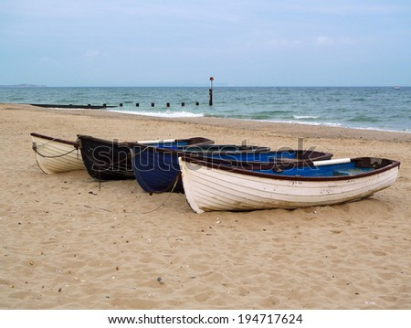 Rowing boats; small clinker-built rowing boats on sandy beach  - stock photo