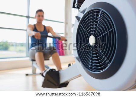 Rowing machine being used in fitness studio - stock photo
