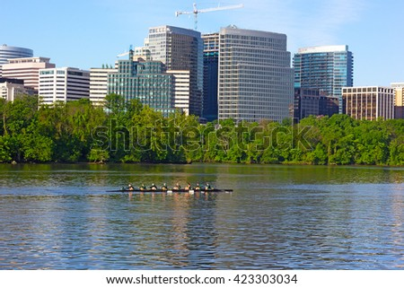 Rowing on Potomac River in the morning. Sunrise over the skyscrapers in Washington DC, USA. - stock photo