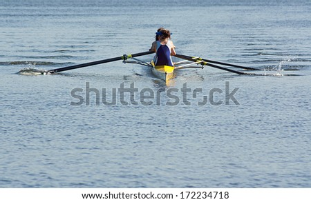 Rowing team working in unison to compete in a regatta by racing specially built row boats - stock photo