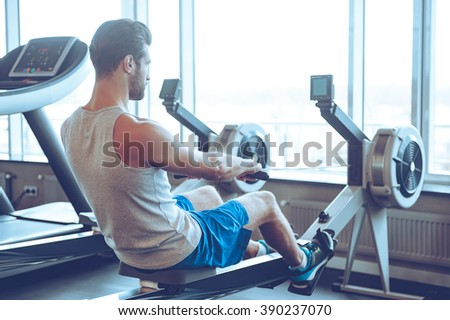 Rowing to success. Side view of young man in sportswear doing rowing in front of window at gym - stock photo