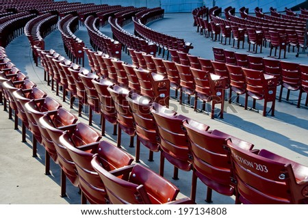 Rows and rows of empty red stadium seats. - stock photo