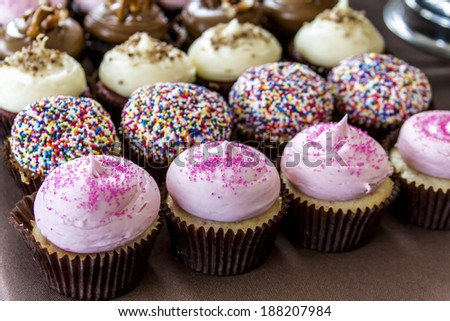 Rows of assorted cupcakes sitting on table with brown tablecloth