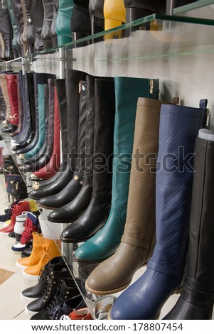 Rows of beautiful, elegant, colored female boots on store shelves.