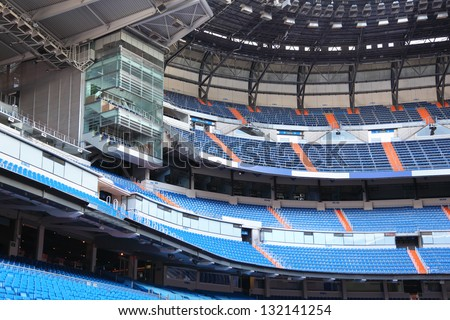 Rows of blue seats for fans at empty large football stadium. - stock photo