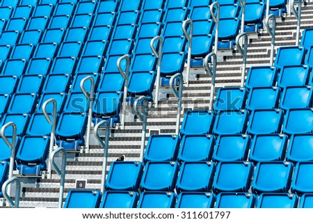 rows of blue seats in a stadium