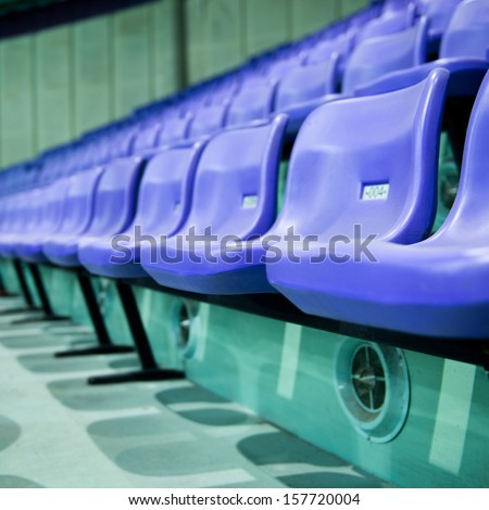 Rows of blue stadium seats with numbers. - stock photo