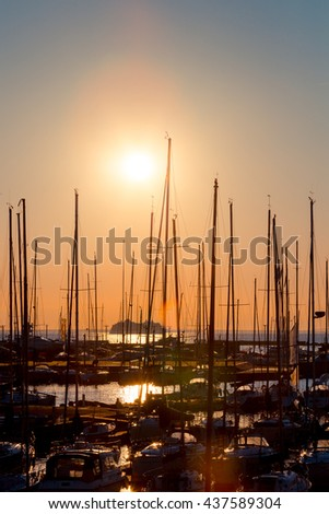 rows of boats at pier in the evening against sunset skies (sunset dusk lighting) - stock photo