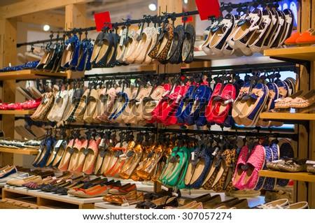 Rows of bright woman shoes on hangers and shelves in store - stock photo