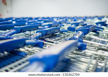 Rows of bunch  shopping carts with blue handles in supermarket