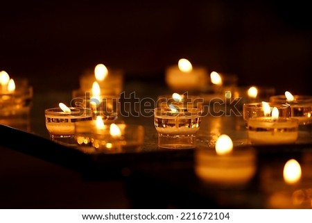 Rows of burning candles in a dim church - stock photo