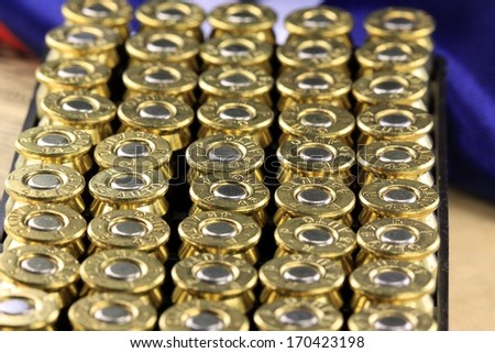 Rows of 45 caliber ammunition copper plated bullets with US flag in background