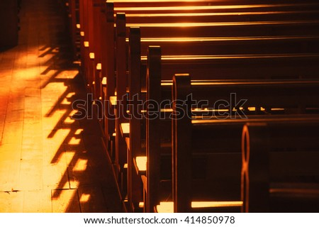 Rows of church benches. Sunlight filtered through the stained glass window. Selective focus. - stock photo