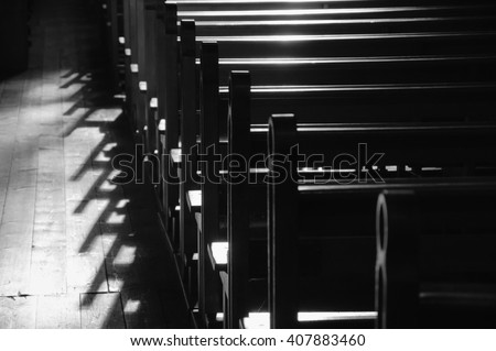 Rows of church benches. Sunlight filtered through the stained glass window. Selective focus. Black and white. - stock photo