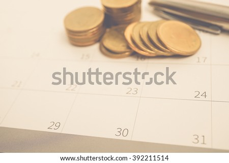rows of coins and pen on calendar for finance and banking concept