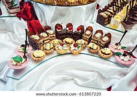 rows of different cakes on a glass stand