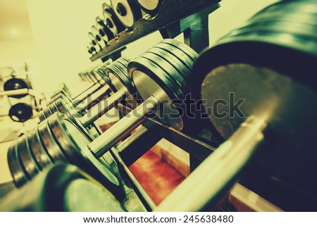 Rows of dumbbells in the gym trough an retro photo filter - stock photo