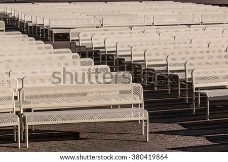 Rows of empty audience benches with a center aisle facing right. - stock photo