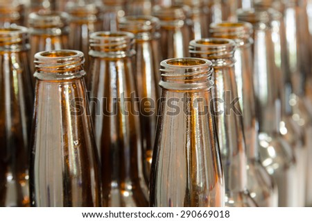 Rows of empty beer bottles lined up by sink  for home brewing - stock photo