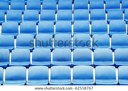 Rows of empty blue color plastic stadium seating on the terrace. - stock photo
